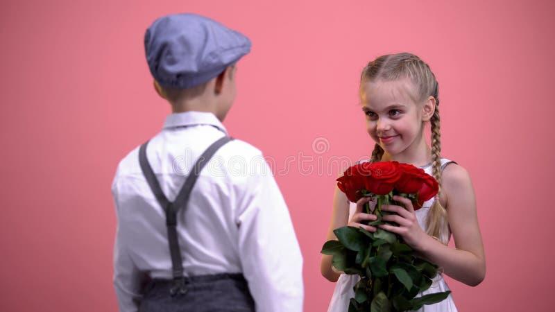 献玫瑰花束的正装的年轻绅士对一点女性 库存图片
