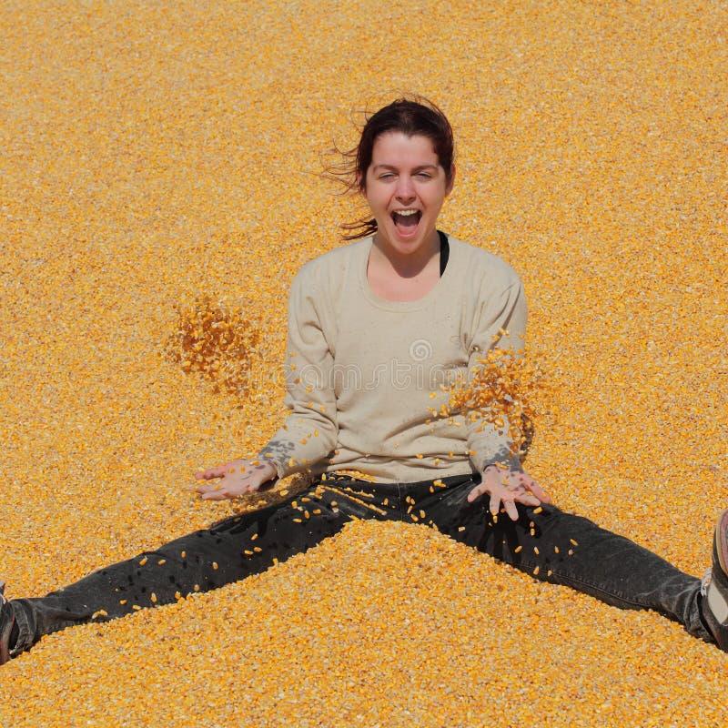 玉米堆的微笑的女孩在收获以后的 免版税库存图片