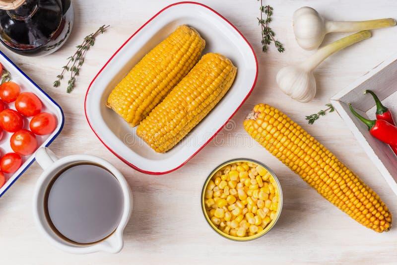 玉米汤或炖煮的食物的成份:玉米穗在白色木背景的,罐装和煮熟的玉米、调味料和菜汤 库存照片