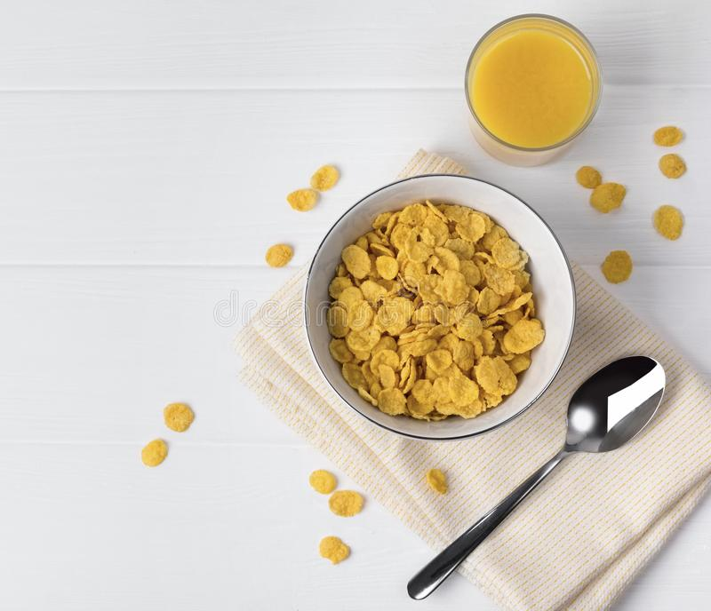 玉米片和杯汁液在白色桌上 库存图片