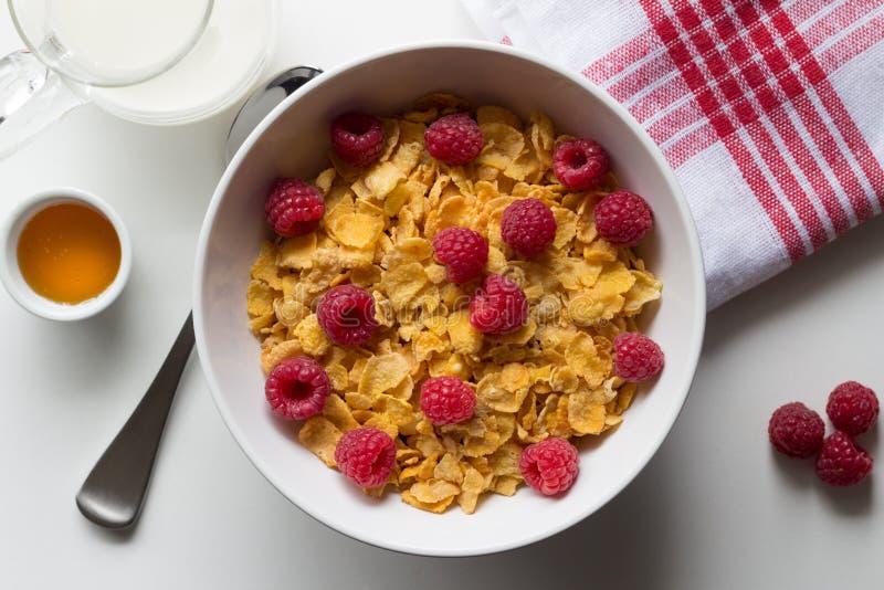 玉米片和莓、蜂蜜和牛奶o早餐谷物  免版税库存图片