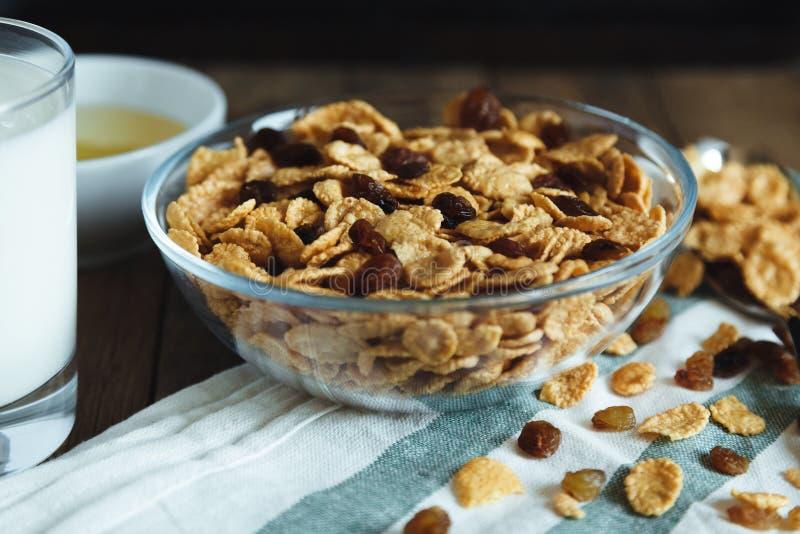 玉米片用在碗的葡萄干在一张木桌上 图库摄影