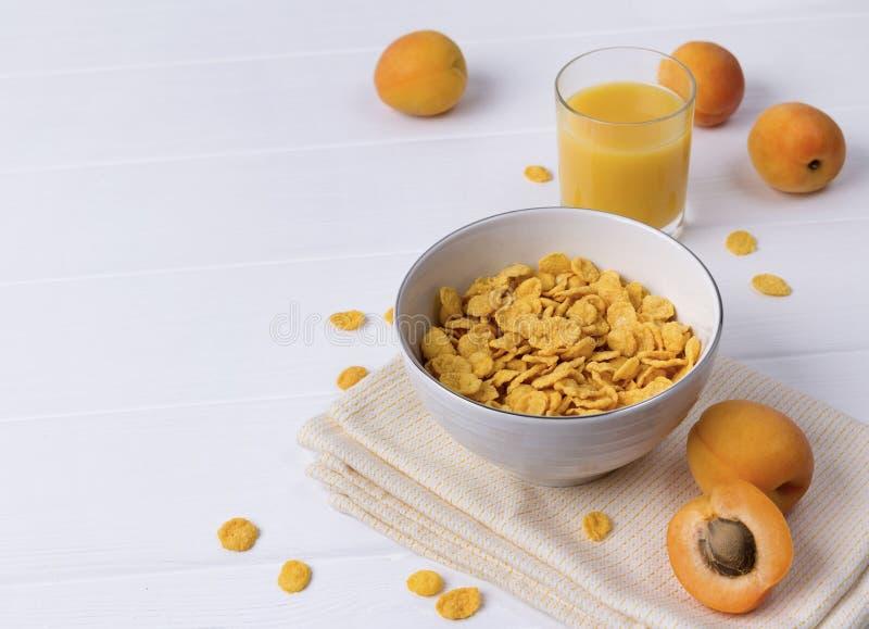 玉米片用杏子在白色木桌上 库存照片