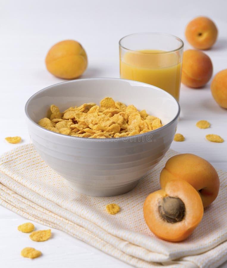 玉米片用杏子在白色木桌上 图库摄影