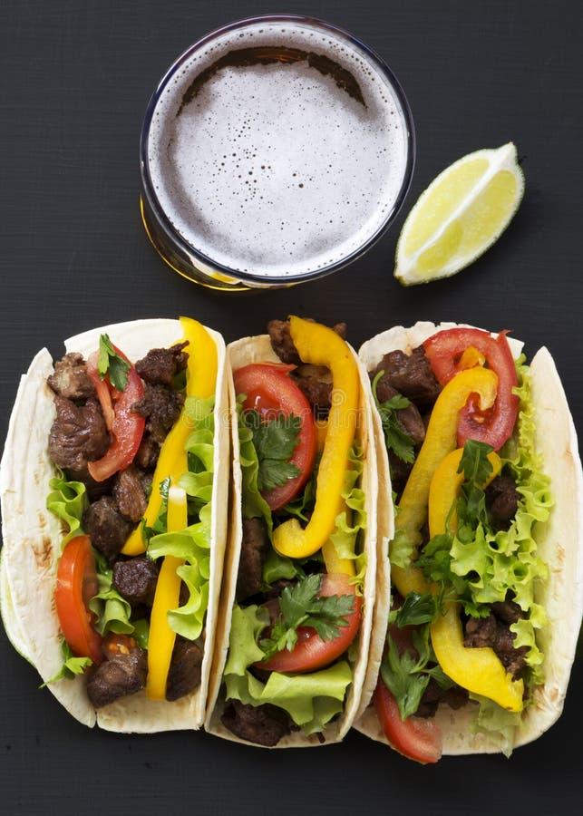 玉米粉薄烙饼用牛肉和菜、啤酒和石灰在黑背景,顶视图 墨西哥厨房 复制空间 平的位置 库存照片