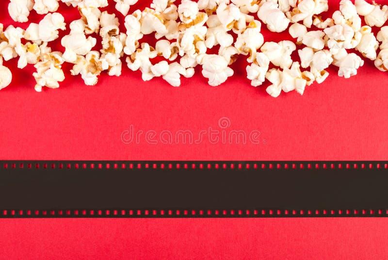 玉米花和影片磁带的关闭在红色背景、顶视图和空间文本的 免版税库存图片