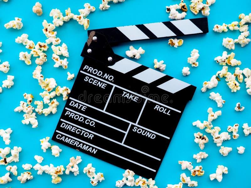玉米花和clapperboard在蓝色背景 电影,影片,娱乐,广告的概念 免版税库存图片