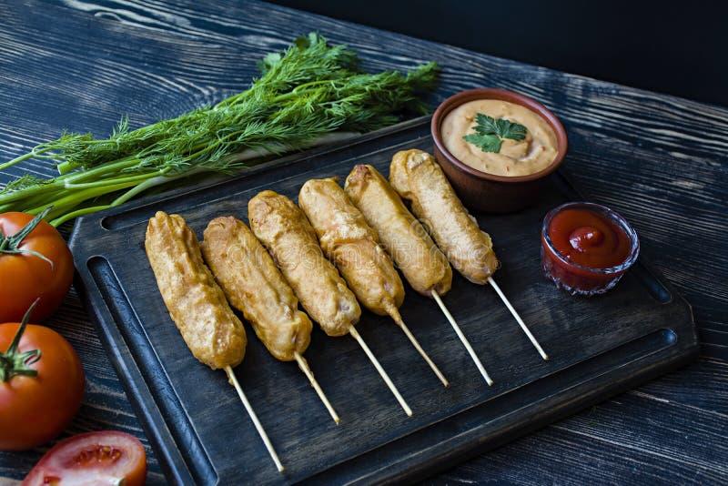 玉米面热狗是美国的传统烹调 油煎的香肠用调味汁 装饰了用新鲜的草本和菜在黑暗 库存照片