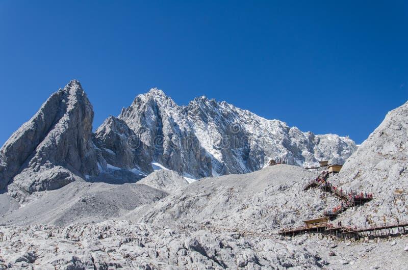 玉龙与步行方式的雪山由上面决定 库存照片