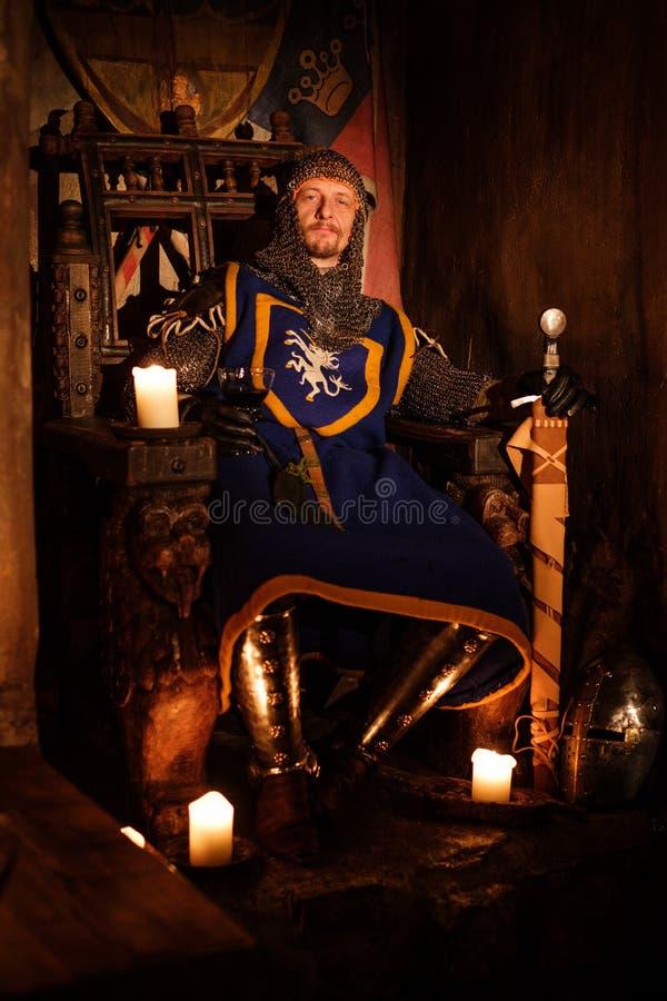 王位的中世纪国王在古老城堡内部 免版税图库摄影