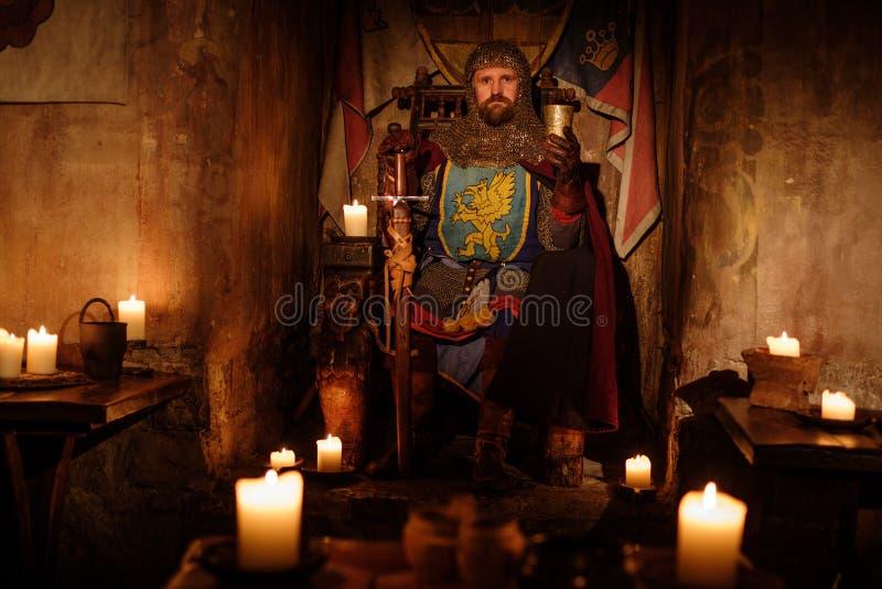 王位的中世纪国王在古老城堡内部 免版税库存照片