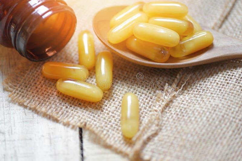 王浆胶囊在木匙子和大袋背景-黄色胶囊医学中或从自然的补充食物健康的 免版税库存照片