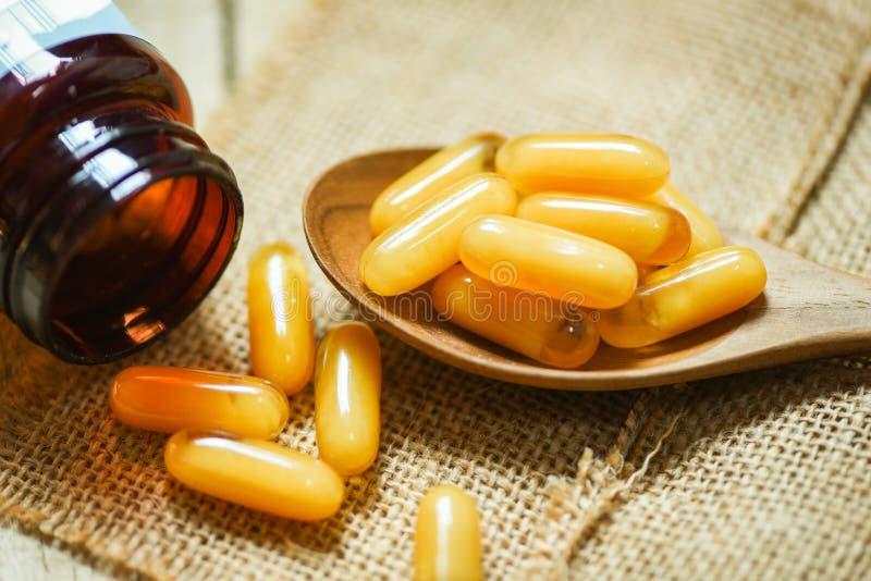 王浆胶囊在木匙子和大袋背景/黄色胶囊医学或者补充食物中 免版税库存图片