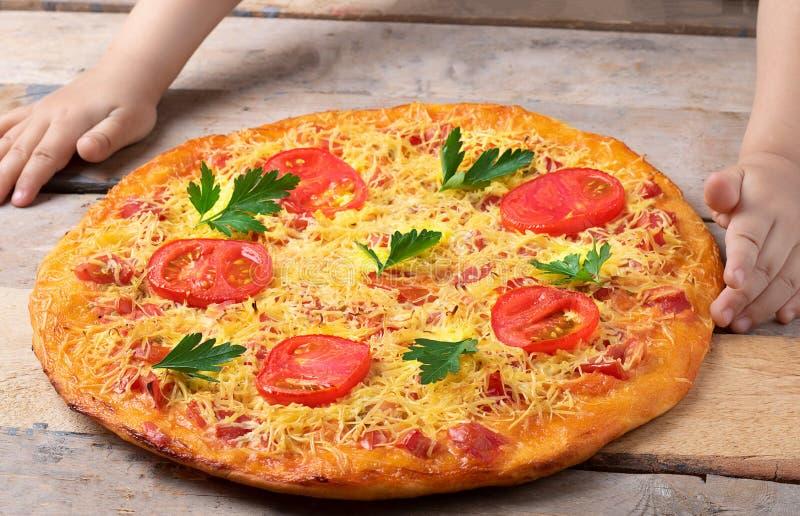 玛格丽塔酒比萨用在木桌上的孩子手,顶视图 库存图片