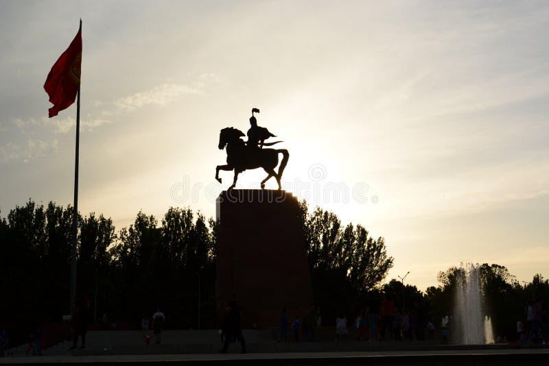 玛纳斯在日落的雕象剪影 太方形的丙氨酸 比什凯克 r 免版税图库摄影