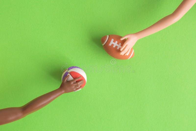 玩偶手平的位置对体育球抽象负的被隔绝在绿色 库存照片