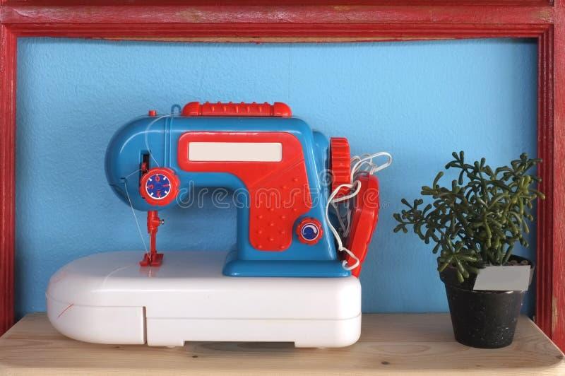 玩具和葡萄酒缝纫机在蓝色背景 免版税库存图片