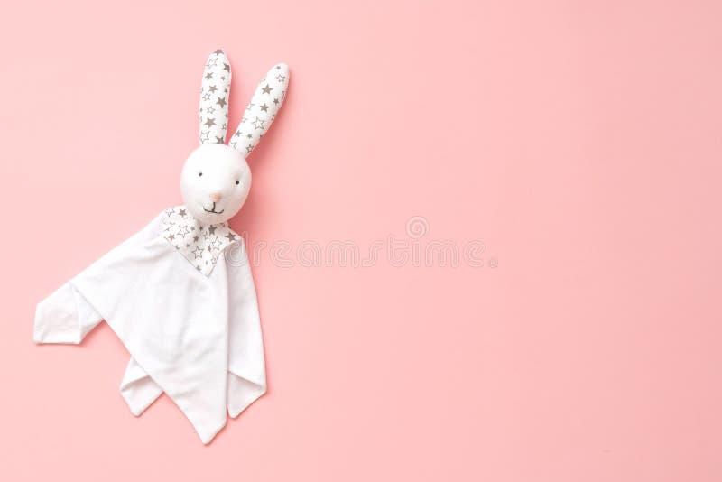 玩具在桃红色背景的橡皮奶嘴兔宝宝 掌握的婴孩的手得心应手的玩具 免版税库存照片