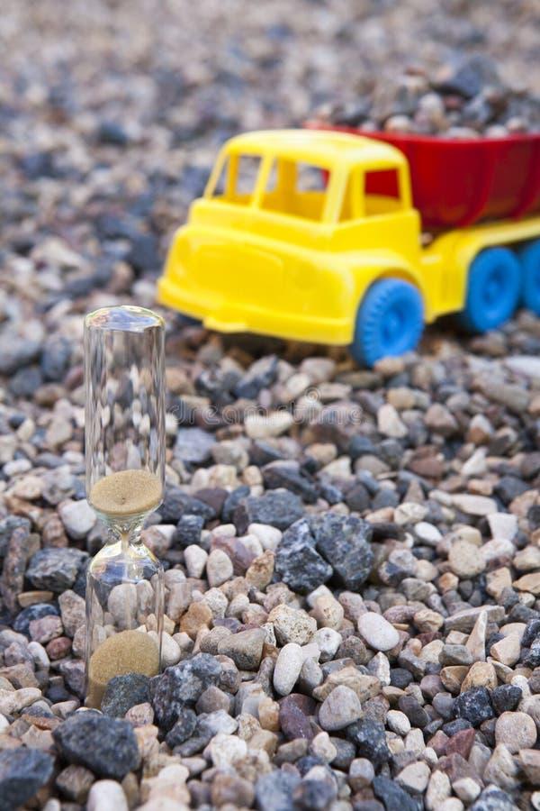 玩具塑料汽车沙子时钟石头背景没人 库存照片