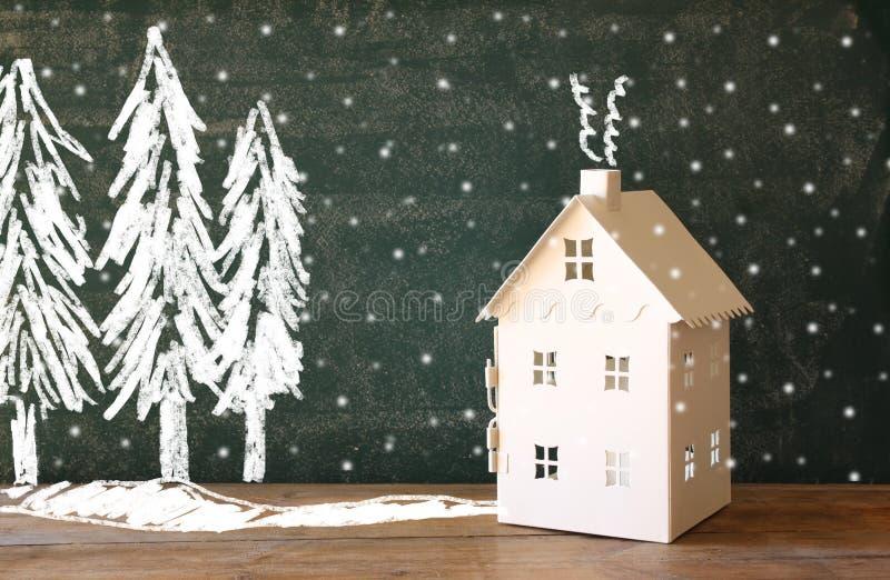 玩具房子照片在黑板前面的有冬天概念图画的 免版税库存照片