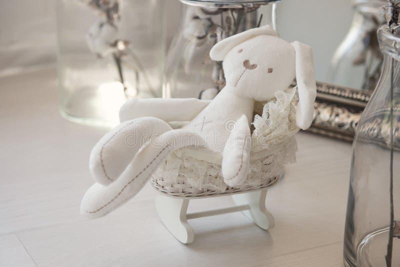 玩具新生儿 在一个小的儿童车的白色兔子 免版税库存照片