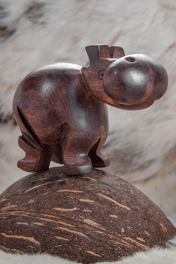 玩具木棕色河马在轻的背景皮肤的一个椰子站立 免版税库存照片