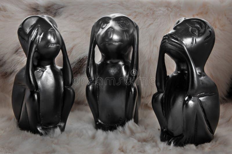 玩具木黑三小的动物,没看见,听不到,不发表演讲关于轻的背景 免版税库存图片