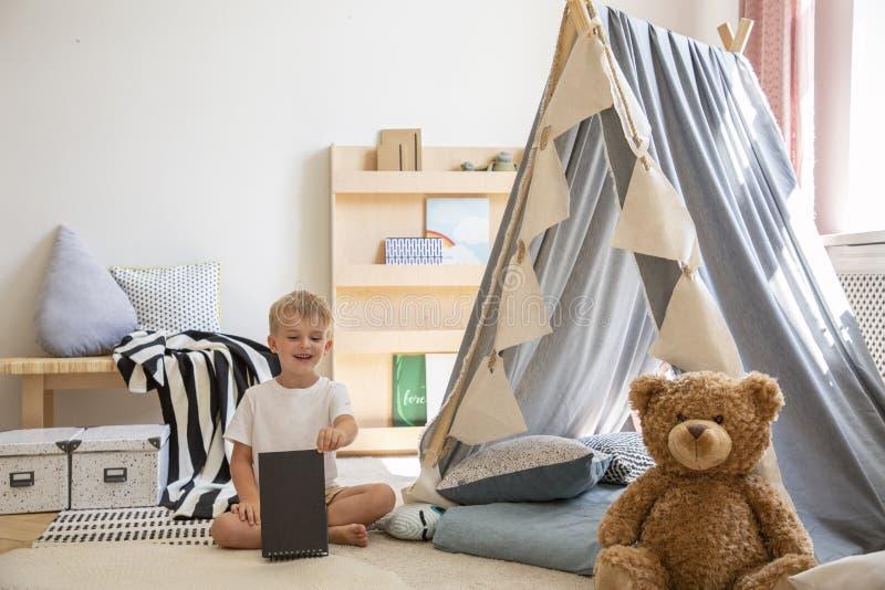玩具熊和帐篷在一个年轻男孩使用的游戏室内部 库存照片