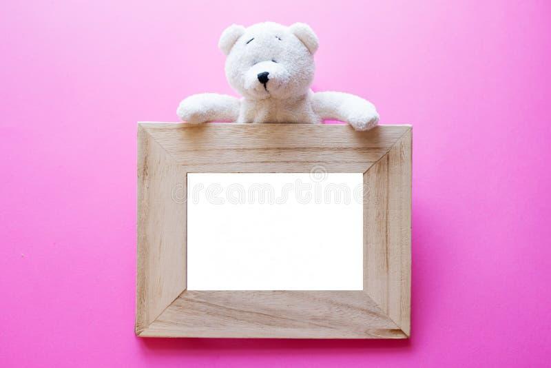 玩具熊和木相框在桃红色背景 孩子的框架 生日概念 库存图片