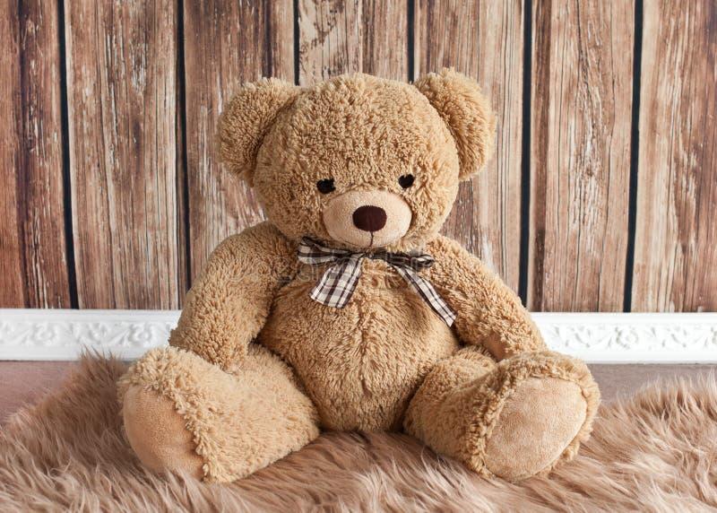玩具熊坐一个蓬松地毯 免版税图库摄影