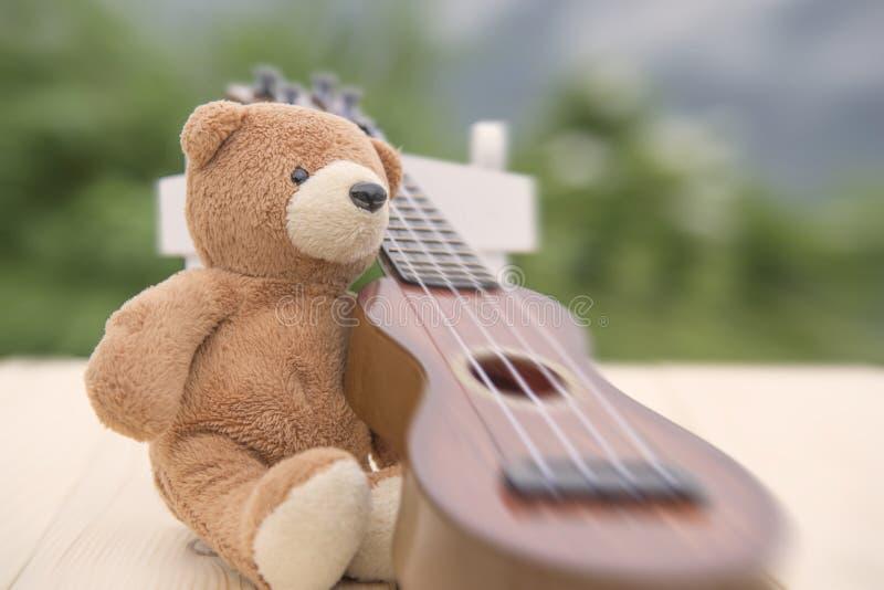 玩具熊坐与被弄脏的尤克里里琴的一把椅子 库存照片