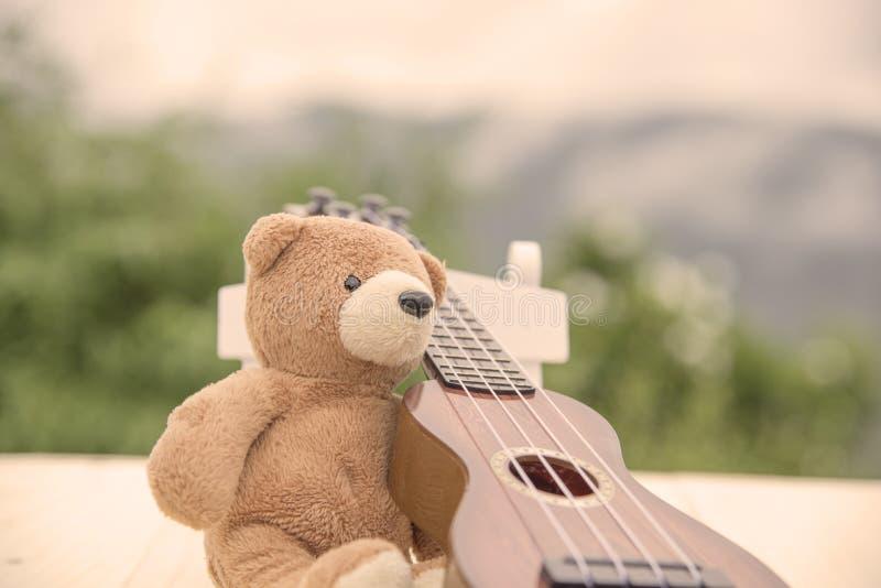 玩具熊坐与被弄脏的尤克里里琴的一把椅子 库存图片