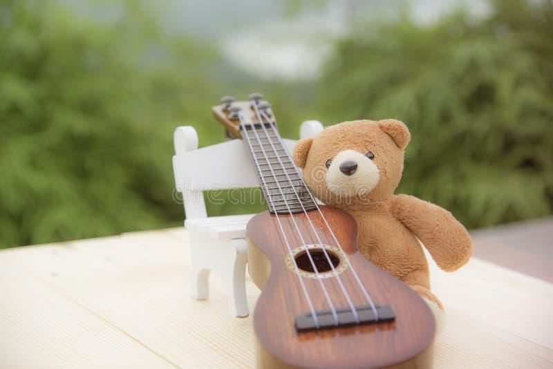 玩具熊坐与被弄脏的尤克里里琴的一把椅子 免版税库存照片