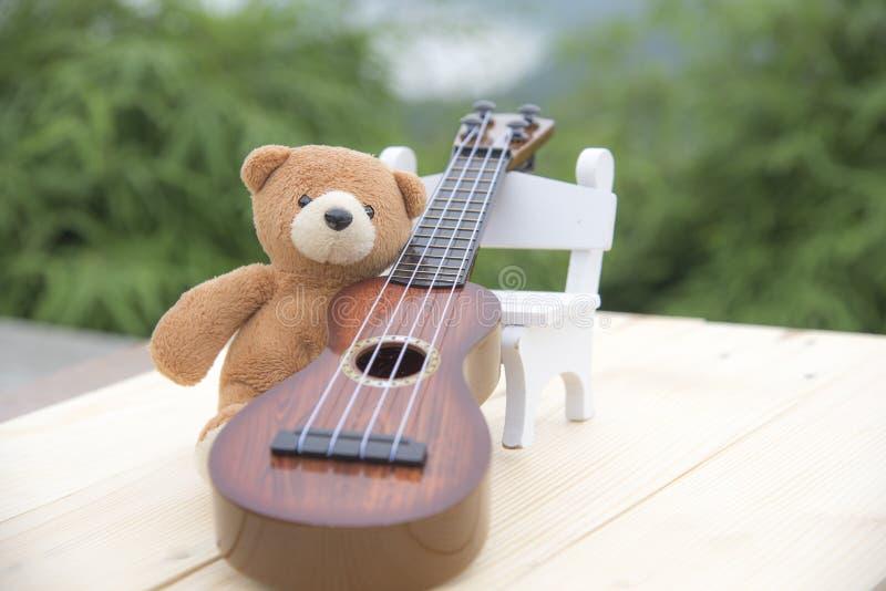 玩具熊坐与被弄脏的尤克里里琴的一把椅子 免版税库存图片
