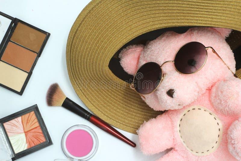 玩具熊有可爱的桃红色 投入在黑eyewear用化妆用品组成,有一个美丽的黄色帽子,白色背景 免版税库存图片
