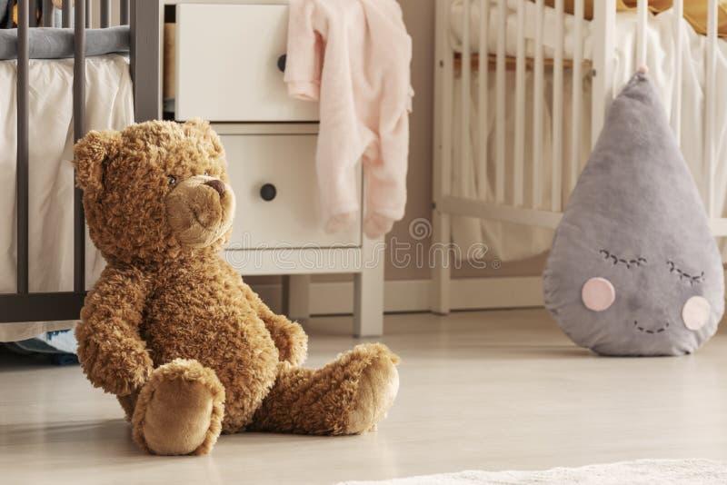 玩具熊特写镜头坐别致的婴孩卧室地板孪生的 免版税库存图片