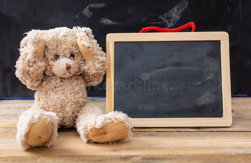玩具熊覆盖物耳朵和一个空白的黑板,文本的空间 库存图片
