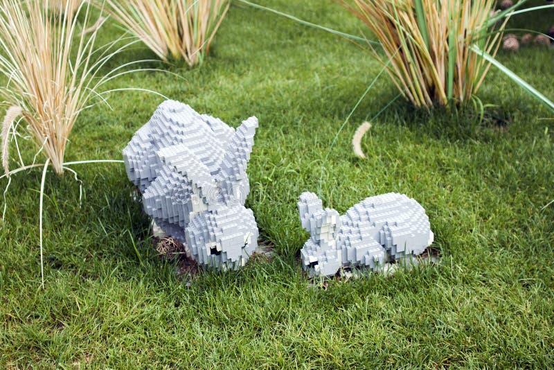 玩具砖吃在草坪的兔子家庭有草 免版税库存照片
