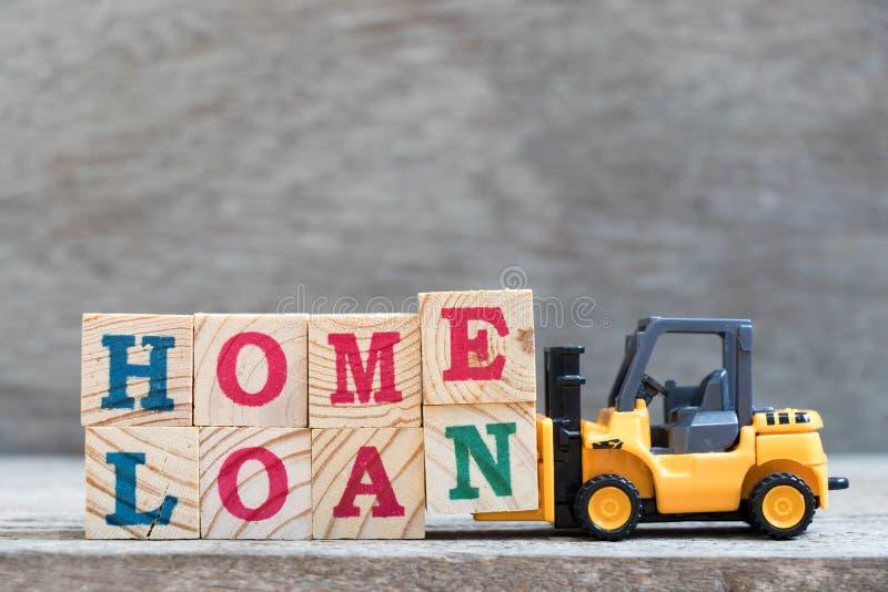 玩具铲车举行信件块措辞房屋贷款的E和N 库存图片