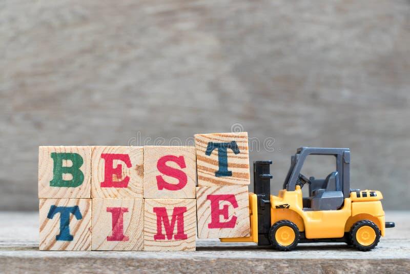 玩具铲车举行信件块措辞最佳的时间的T和E 库存图片