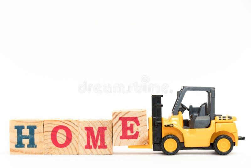 玩具铲车举行完成白色背景的词家的信件块E 库存照片