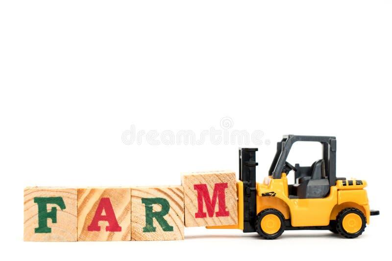玩具铲车举行完成词农场的信件块M 库存照片