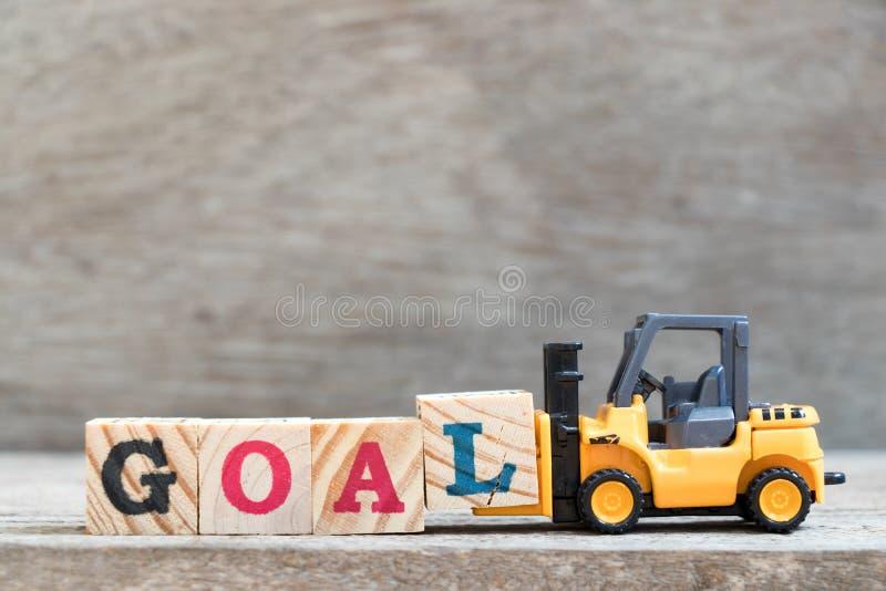 玩具铲车举行完成词目标的信件块L 免版税库存图片