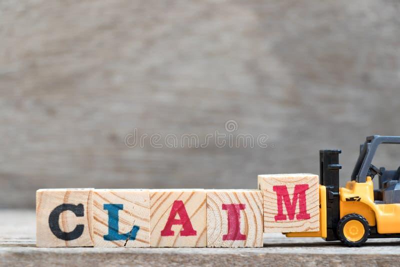 玩具铲车举行完成词要求的信件块M 库存照片