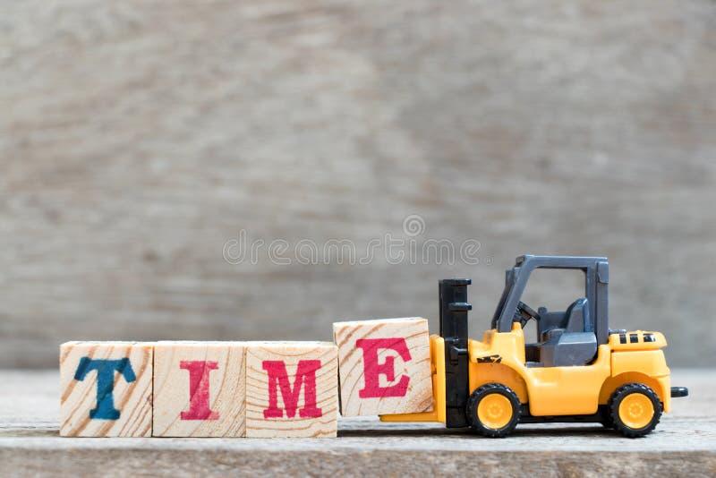 玩具铲车举行结束字时间的信件块E 图库摄影