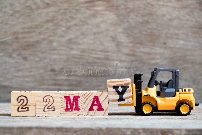玩具铲车完成词的举行块Y 22可以 免版税图库摄影