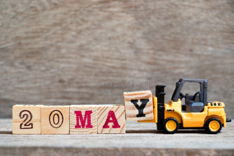 玩具铲车完成词的举行块Y 20在木背景& x28可以;概念为历日的月May& x29; 库存图片