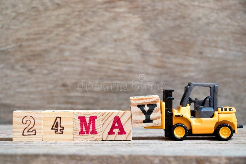 玩具铲车完成词的举行块Y 24在木背景& x28可以;概念为历日的月May& x29; 免版税库存照片