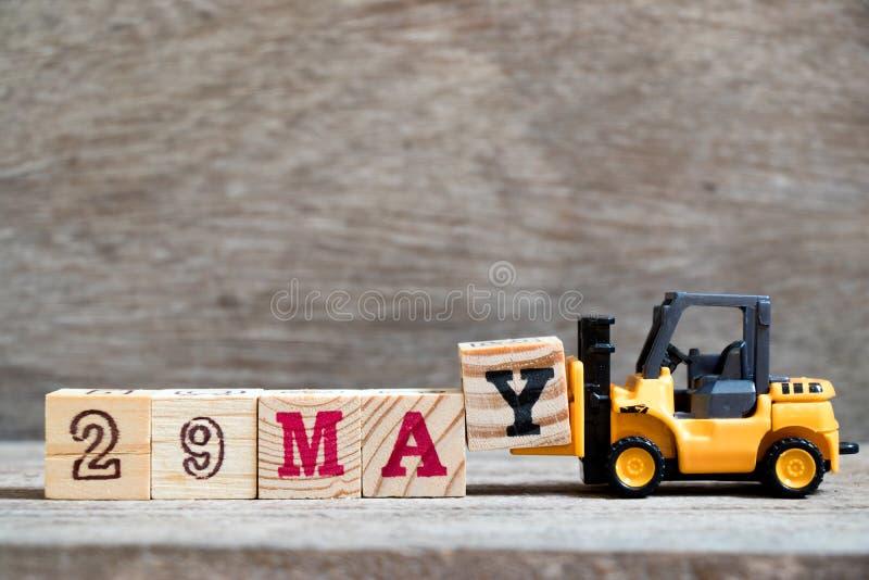 玩具铲车完成词的举行块Y 29在木backgr可以 免版税库存图片