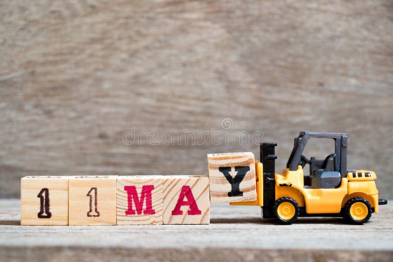 玩具铲车措辞11的举行块Y在木背景概念可以为历日的月5月 库存照片